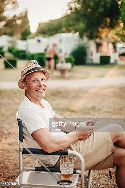 Man camping in his caravan playing with smart phone