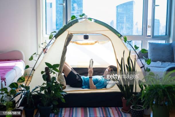 彼のリビングルームでキャンプをする男 - レクレーション活動 ストックフォトと画像