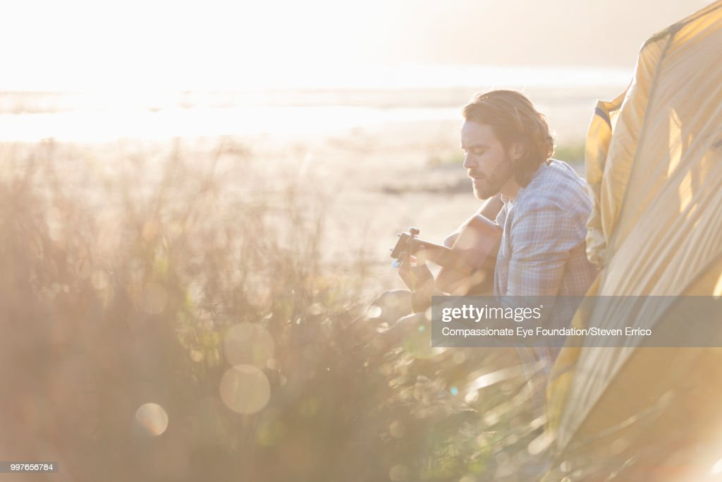 Man camping playing guitar on beach at sunset : Stock Photo