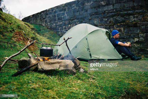 man camping sitting at a tent next to a mountain stream and ancient bridge making a fire with a kettle - human limb stock pictures, royalty-free photos & images