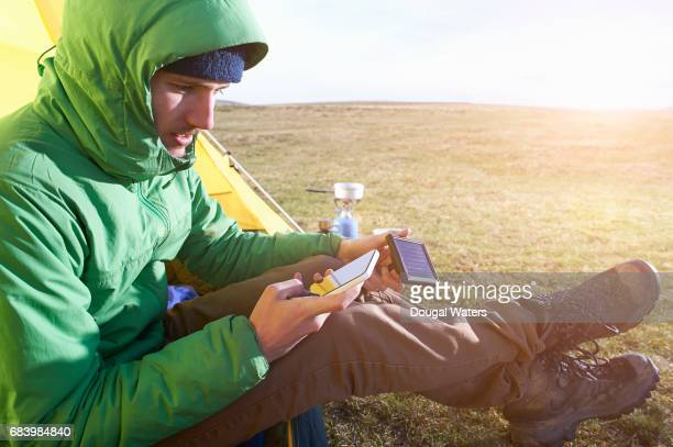Man camping using portable solar panel to charge phone.