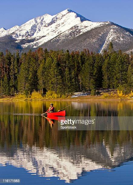 Mann Kanufahren und Fliegenfischen auf dem Colorado Lake