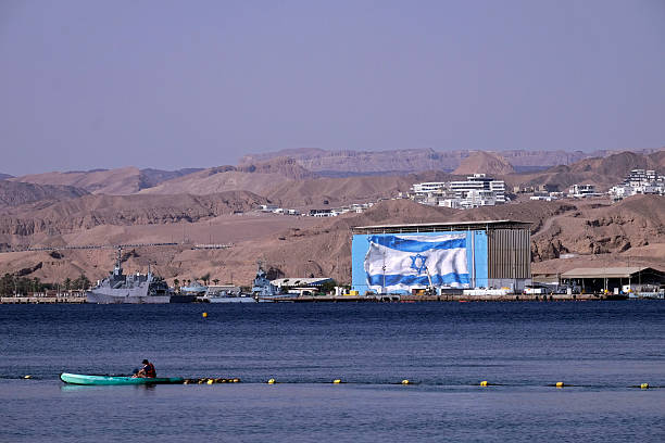 A man canoeing at the northern shore of the city of Eilat with Sa'ar 5 class missile сorvettes of the Israeli Navy in background at the northern tip of the Red Sea in Israel