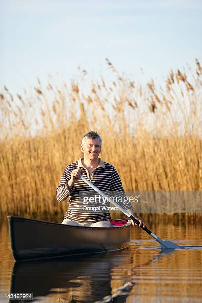 Man canoeing in lake.