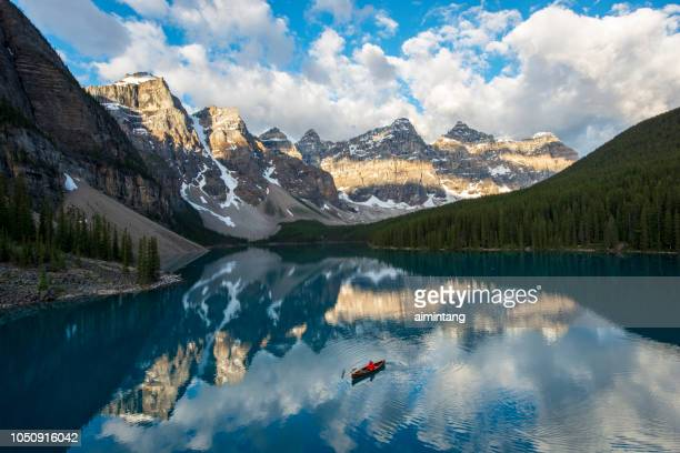 a man canoeing in moraine lake with first morning light on ten peaks in banff national park - valley of the ten peaks stock pictures, royalty-free photos & images