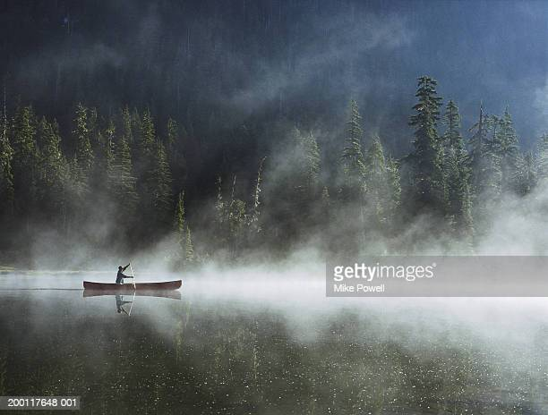 Man canoeing on lake cover with fog, side view
