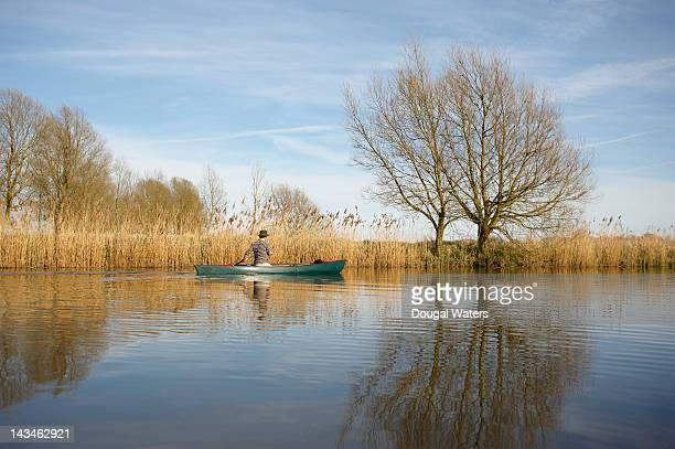 man canoeing on lake in countryside. - dougal waters stock pictures, royalty-free photos & images