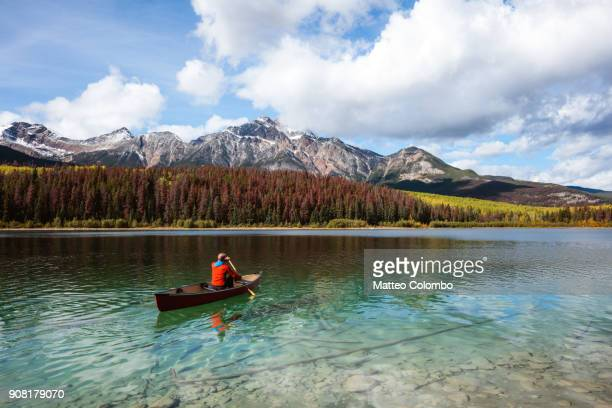 man canoeing on lake, jasper national park, canada - canadian rockies stockfoto's en -beelden