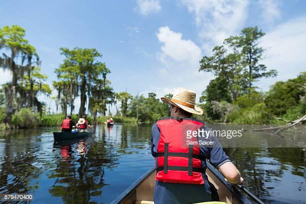 man canoeing through wetlands in louisiana - sumpf stock-fotos und bilder
