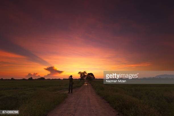 A man capturing beautiful colors during sunrise with phone.