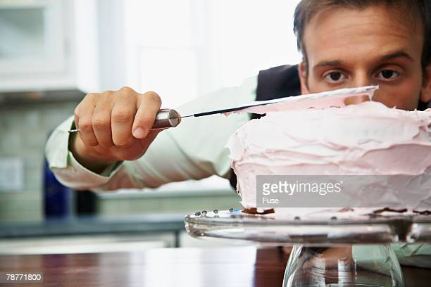 Man Carefully Icing a Cake