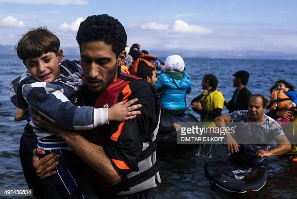 A man caries a child as they arrived with others refugees and migrants on a rubber boat on the Greek island of Lesbos after crossing the Aegean sea...