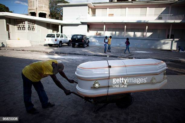 A man caries a coffin at the city hospital on January 16 2010 in PortauPrince Haiti Haiti is trying to recover from a powerful 70strong earthquake on...