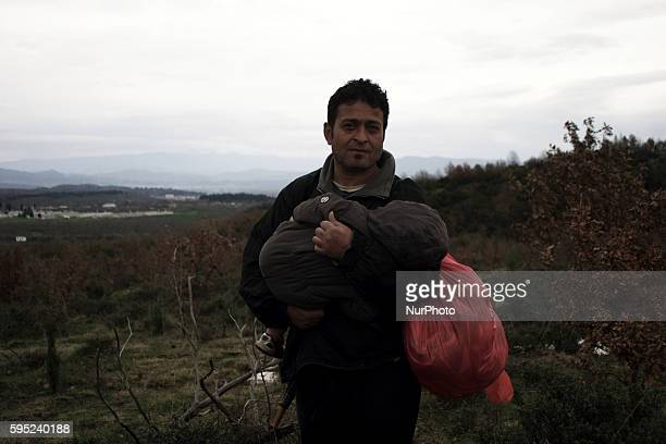 A man caries a tray of tea in a makeshift camp on March 14 2016 at the GreekMacedonian border near the Greek village of Idomeni where thousands of...