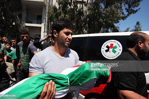 A man caries one of the bodies of three children who lost his live due to a fire in a house from morgue of Sifa Hospital in Gaza City Gaza on May 7...