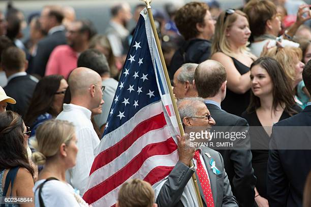 A man caries the US flag during the 15th Anniversary of September 11 at the 9/11 Memorial and Museum Sunday September 11 2016 in New York The United...