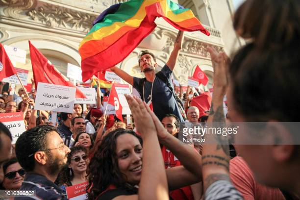 Man carried on shoulders waves the rainbow flag during the celebration of the National Womens Day in avenue Habib Bourguiba in Tunis, on August 13,...