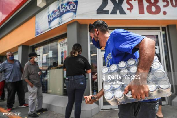 A man carries a 24 beer package while omiting the social distancing measures on May 1 2020 in Hermosillo Mexico A few stores in Hermosillo and the...