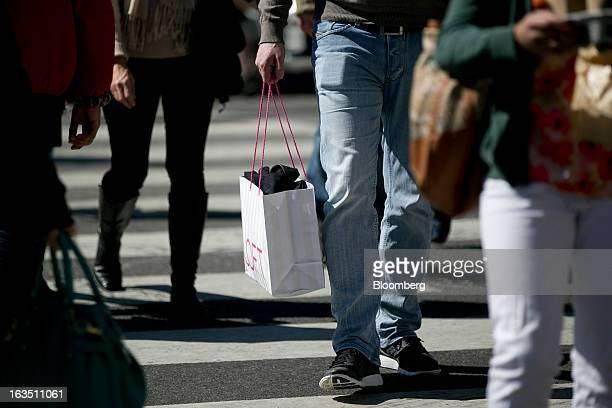 A man carries a Ann Taylor Inc Loft shopping bag in the Georgetown neighborhood of Washington DC US on Saturday March 9 2013 The US Census Bureau is...