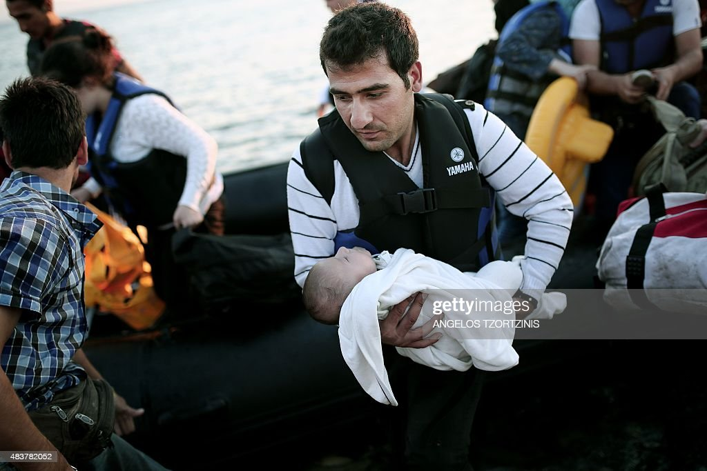 A man carries a baby out of an inflatable boat carrying migrants who arrived on the Greek island of Kos after crossing a part of the Aegean Sea between Turkey and Greece on August 13, 2015. Greece sent extra riot police to Kos as tensions mounted over a huge influx of migrants. The Greek government said it was 'immediately' dispatching a ship to Kos to double up as an accommodation and processing centre for up to 2,500 people as around 7,000 migrants wait to apply for immigration papers.