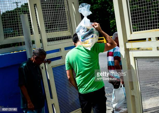 A man carries a bag of basic foodstuff as he leaves one of the food distribution centers called CLAP which are run by community leaders in Caracas on...