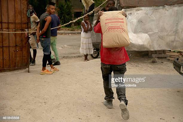 A man carries a bag of cement out of a building supply yard in the Vedado neighborhood of Havana January 20 2015 in Havana Cuba There are 43 of these...