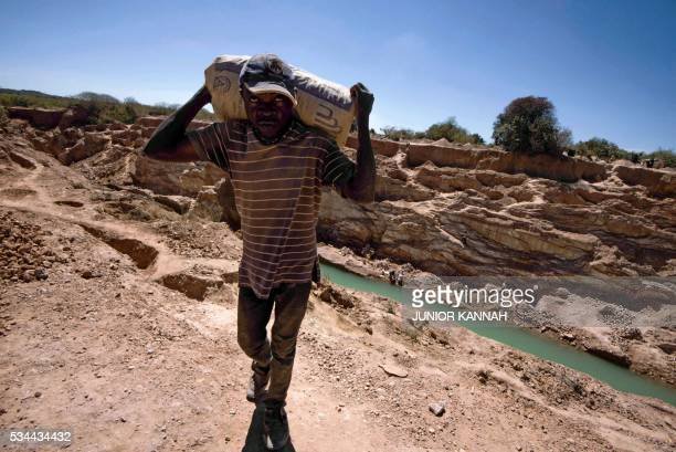 A man carries a bag of copper at a mine quarry and cobalt pit in Lubumbashi on May 23 2016 The price of copper has fallen heavily directly impacting...