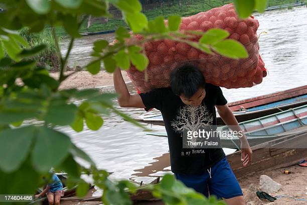 A man carries a bag of potatoes at an illegal trading point on the Moei River marking the border between Thailand and Myanmar