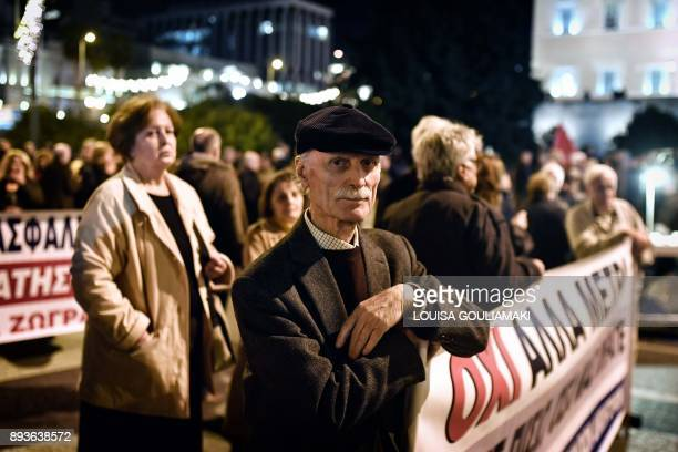 A man carries a banner as Greek pensioners demonstrate in front of the Greek parliament in Athens on December 15 2017 Pensioners' associations from...