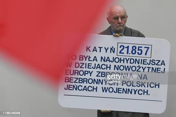 A man carries a banner in relation to Katyn massacre on Polish military officers carried out by the Soviet Union seen during a procession from Wawel...