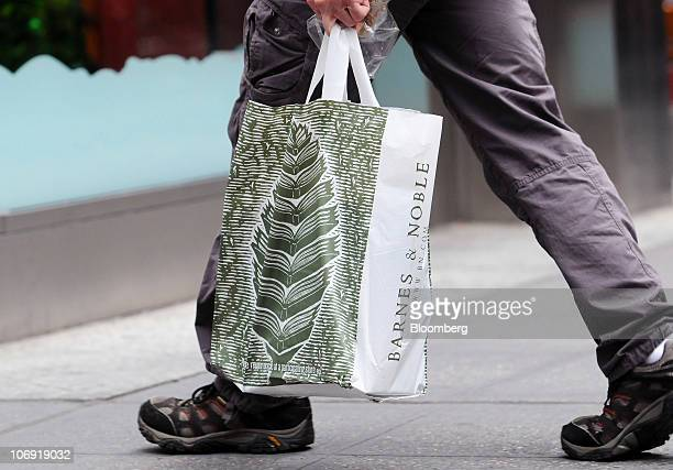 A man carries a Barnes Noble shopping bag along Fifth Avenue in New York US on Tuesday Nov 16 2010 Barnes Noble Inc has a special shareholder meeting...
