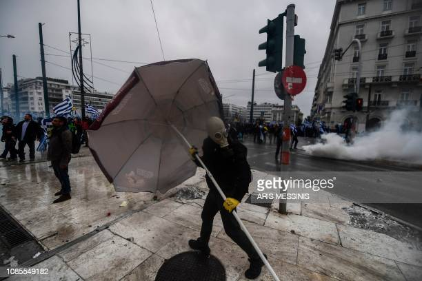 A man carries a beach umbrella as protesters clash with riot police in front of the Greek Parliament in Athens on January 20 2019 during a...