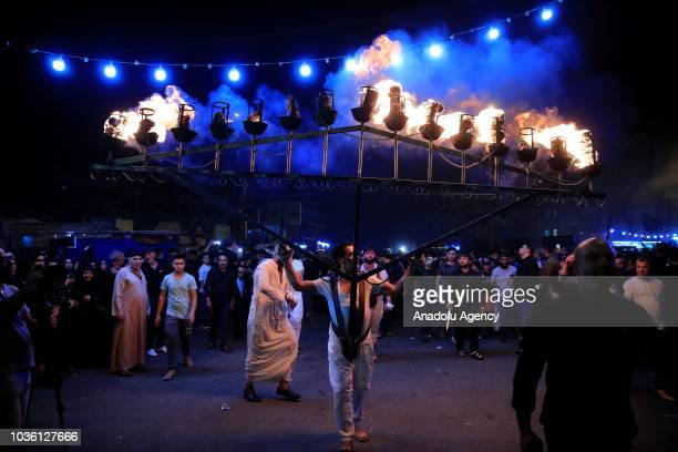 A man carries a big burning candles during the holy month of Muharram commemorations in Baghdad Iraq on September 19 2018 Ashure or Noah's Pudding...