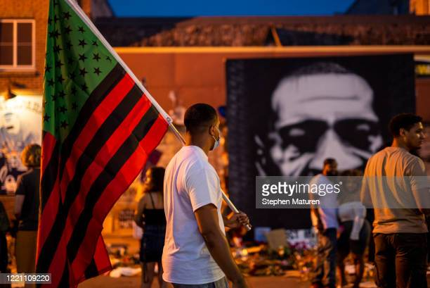 A man carries a Black Liberation flag through a Juneteenth celebration at the memorial for George Floyd outside Cup Foods on June 19 2020 in...