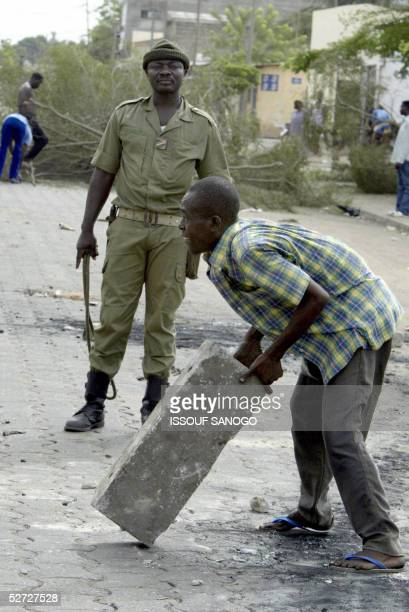 Man carries a block of concrete as he cleans the street under the eyes of a Togolese soldier in Lome 28 April 2005. Calm was returning slowly 28...