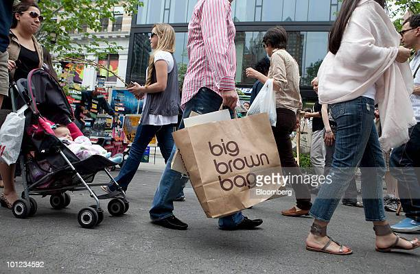 A man carries a Bloomingdale's bag as he walks through Union Square in New York US on Friday May 28 2010 Consumer spending in the US unexpectedly...