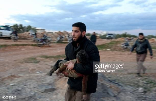 A man carries a body of a child after an airstrike to the deescalation zone of Khan alSabil village in Idlib Syria on January 02 2018 At least 7...