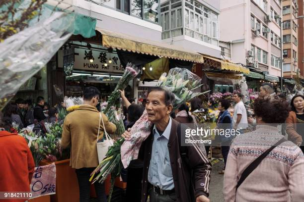 A man carries a bouquet through a flower market ahead of Lunar New Year in the Mong Kok district of Hong Kong China on Wednesday Feb 14 2018 The...