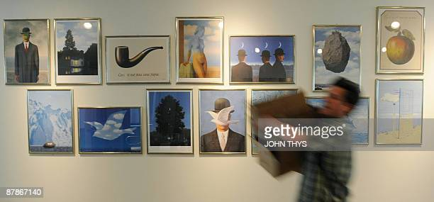 A man carries a box past prints of paintings by the Belgian artiste Rene Magritte at the press opening of the new Margitte museum in Brussels on May...