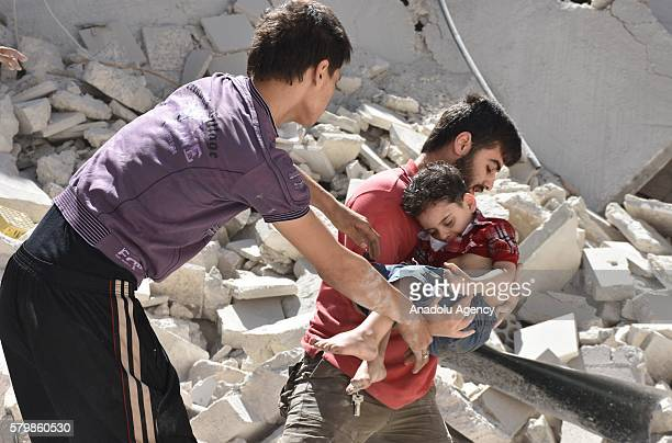 A man carries a boy from the site of a barrel bomb attack staged by Syrian army in the oppositioncontrolled Mashhad district of Aleppo on July 25...