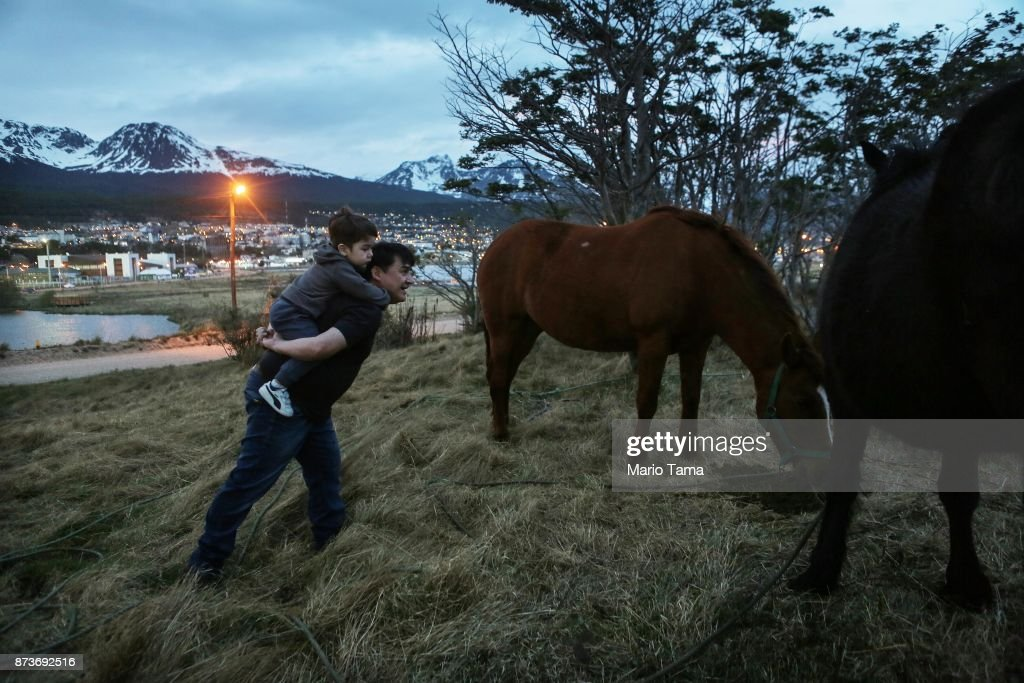 A man carries a boy to watch horses grazing on November 1, 2017 in Ushuaia, Argentina. Ushuaia is situated along the southern edge of Tierra del Fuego, in the Patagonia region, and is commonly known as the 'southernmost city in the world'. The city's main fresh water supply comes from the retreating Martial Glacier, which may be at risk of disappearing. In a 2015 report, warming temperatures led to the loss of 20 percent of the mass and surface of glaciers in Argentina over the previous 50 years, according to Argentina's Institute of Nivology, Glaciology and Environmental Sciences (IANIGLIA). Ushuaia and surrounding Tierra del Fuego face other environmental challenges including a population boom leading to housing challenges following an incentivized program attracting workers from around Argentina. Population in the region increased 11-fold between 1970 and 2015 to around 150,000. An influx of cruise ship tourists and crew, many on their way to Antarctica, has also led to increased waste and pollution in the area sometimes referred to as 'the end of the world'.