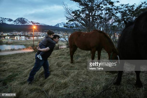 A man carries a boy to watch horses grazing on November 1 2017 in Ushuaia Argentina Ushuaia is situated along the southern edge of Tierra del Fuego...