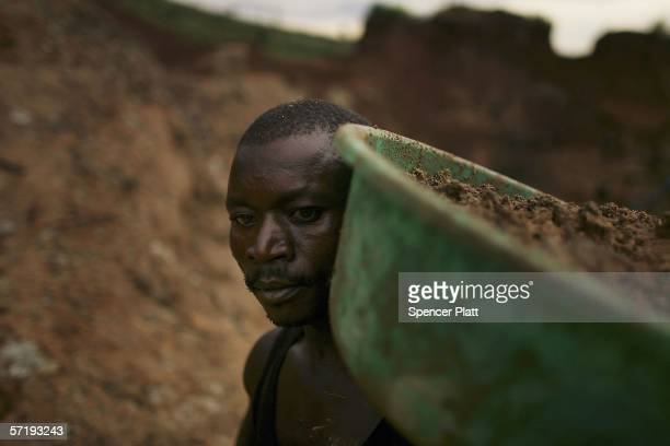 A man carries a bucket of dirt which he will sift through while looking for gold March 27 2006 in Mongbwalu Congo Thousands of Congolese scrape...