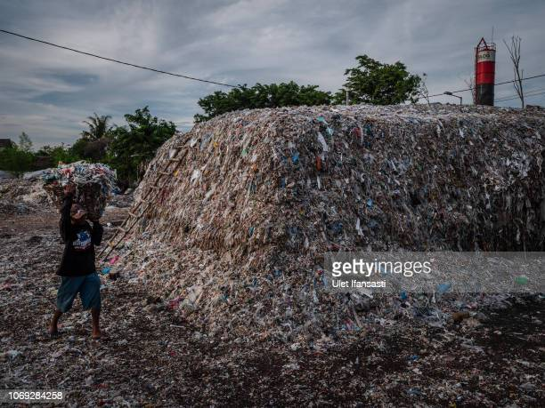 Man carries a bucket of plastic waste to recycle at a import plastic waste dump in Mojokerto on December 4, 2018 in Mojokerto, East Java, Indonesia....