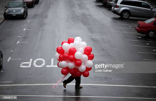 A man carries a bunch of ballons as he walks down Union Street on Valentine's Day on February 14 2011 in San Francisco California Valentine's Day is...