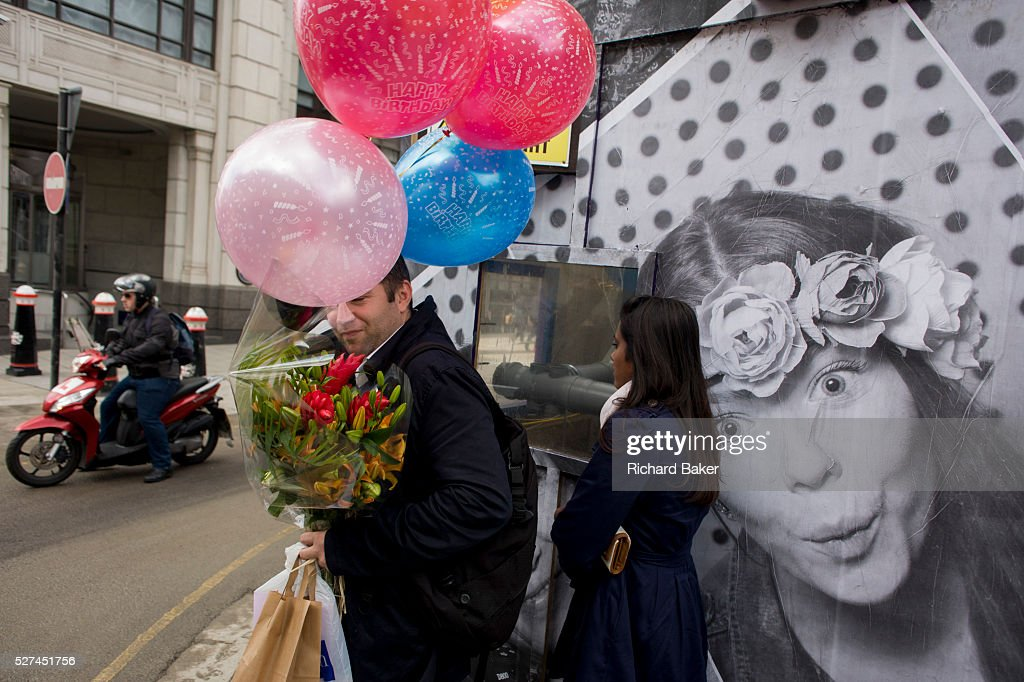 A Man Carries Bunch Of Birthday Balloons And Red Flowers Past Construction Hoarding