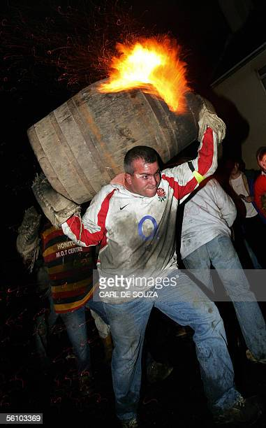 A man carries a burning barrel through the village of Ottery St Mary Devon late 05 November 2005 The tradition of carrying burning wooden barrels...