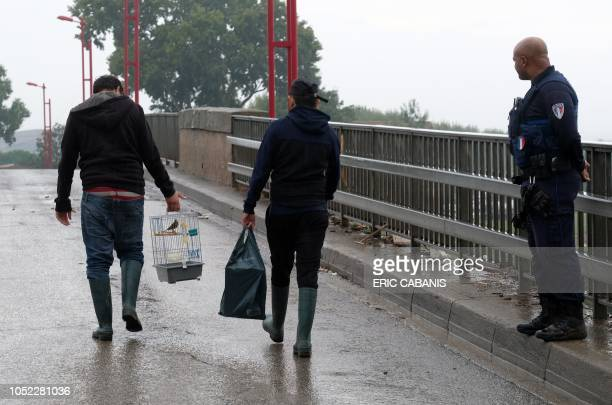 Man carries a cage with a bird in Trebes, near Carcassonne, southern France on October 16, 2018 after the floods. - At least 11 people died when...