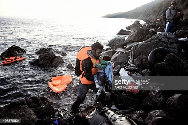 A man carries a child after arriving with other refugees and migrants on the Greek Lesbos island after crossing the Aegean Sea from Turkey on...