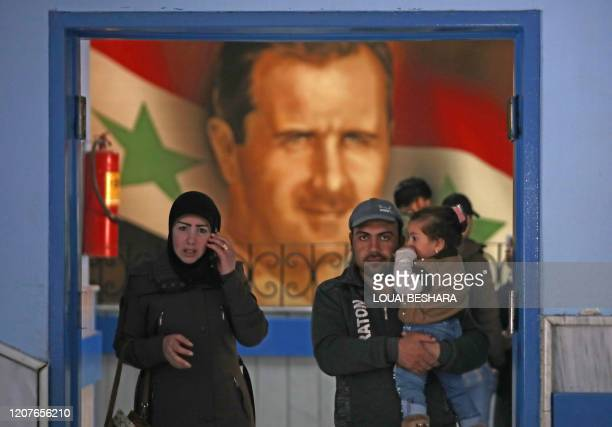 Man carries a child as he and a woman stand in the doorway of a ward at a hospital in the Syrian capital Damascus , on March 19 as it is being...